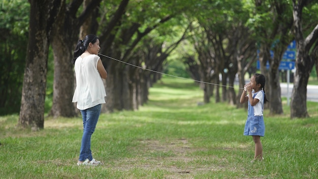 Asian family, mother and daughter doing string phone play activities tie rope at the park