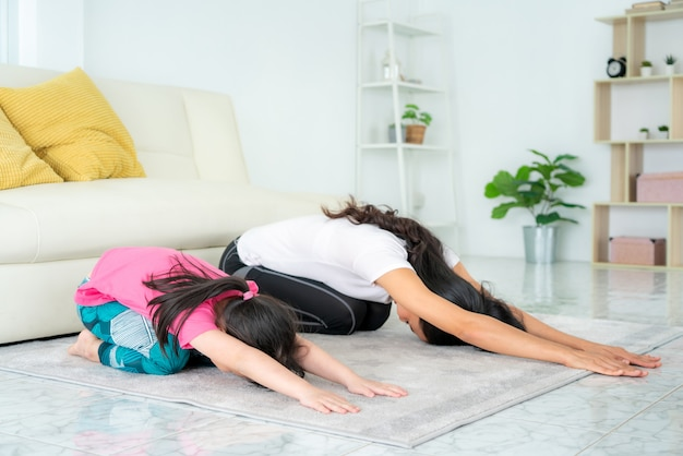 Asian family mother and daughter doing yoga exercises in living room at home