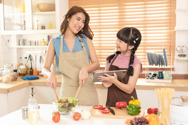Asian family, mother and daughter enjoy cooking prepare salad food together in kitchen room at home.