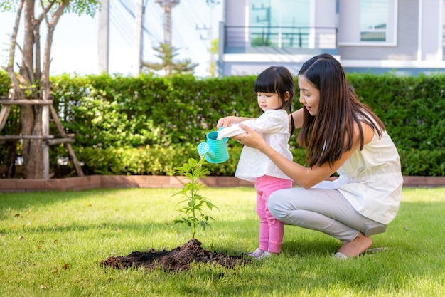 Asian family mother and kid daughter plant sapling tree and watering outdoors in nature spring for reduce global warming growth feature and take care nature earth.