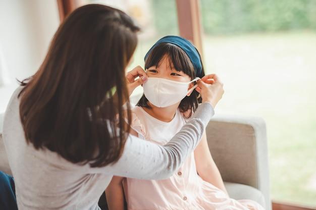 アジアの家族の母親は、コロナウイルスからの保護のために娘の顔にマスクを着用します