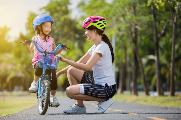 The asian family mother teaching children bicycle at the park