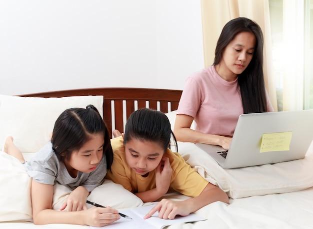 アジアの家族の母親はラップトップのオンライン作業を使用し、彼女の娘は寝室のベッドで宿題をします