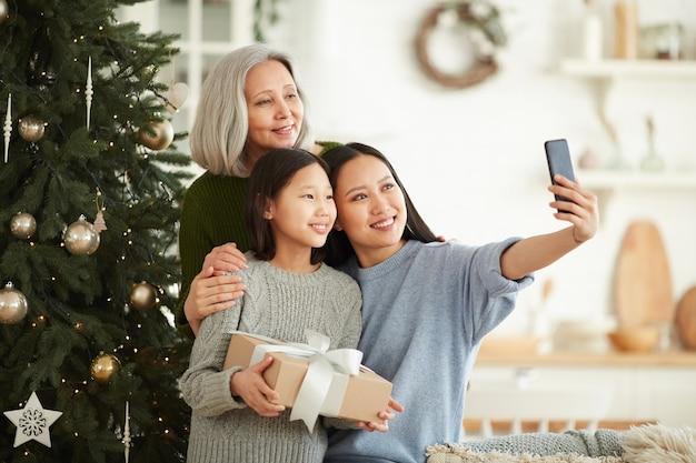 Азиатская семья из трех человек делает селфи-портрет на мобильном телефоне, стоя возле елки во время праздника