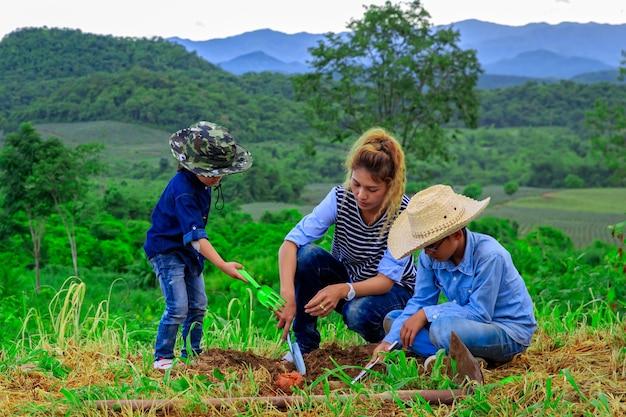산 근처 농장에서 나무를 심는 아시아 가족