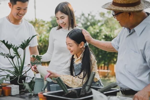 自宅の庭に植樹するアジアの家族。子供と祖父のライフスタイルを持つ親。
