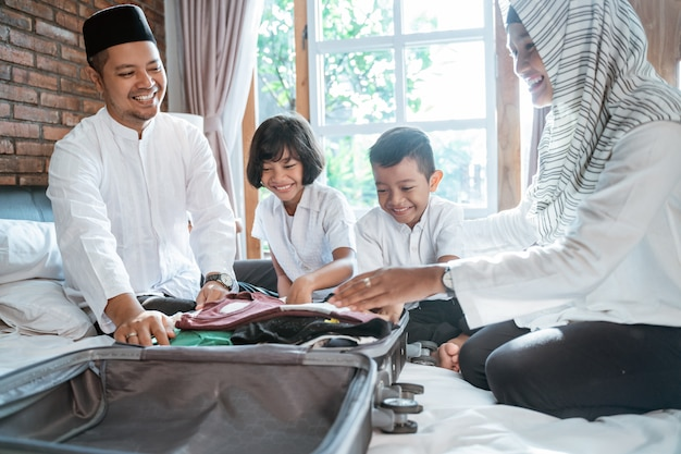 アジアの家族が服を準備してスーツケースに入れる