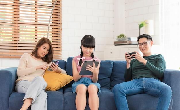 Азиатская семья отдыхает на диване с помощью цифровых технологий смартфонов и гаджетов.