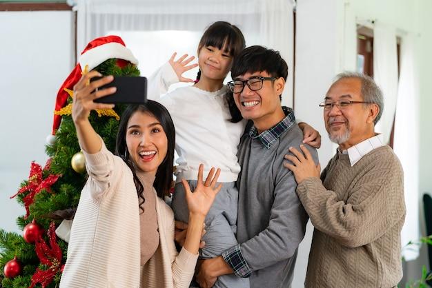 クリスマスツリーとアジアの家族の自分撮り