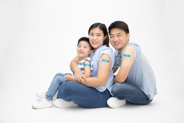 흰색 배경에 고립 된 예방 접종을받은 석고와 팔을 보여주는 아시아 가족