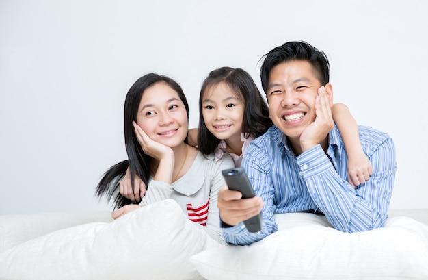 一緒にテレビを見てベッドに座っているアジアの家族