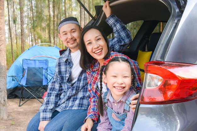자동차 트렁크에 앉아 휴가를 가는 아시아 가족. 자동차로 가족 여행.