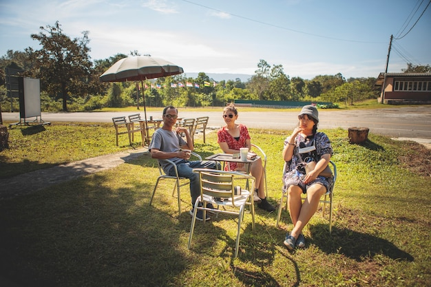 Asian family sitting at outdoor chair