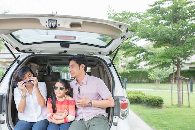 아시아 가족 여름 활동. 아버지, 어머니, 딸은 야외 여행을 위해 차 뒤에 앉아 있습니다.