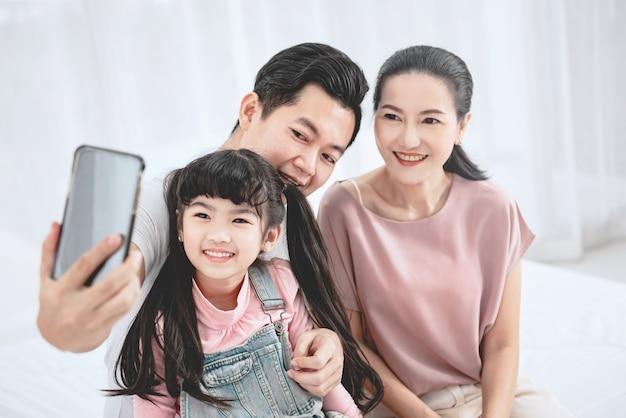 家で自分撮りをしているアジアの家族