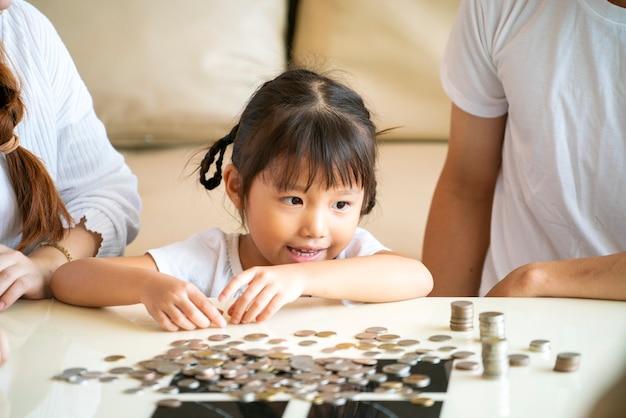 아시아 가족은 유리 은행에 동전을 넣어 돈을 절약 아시아 귀여운 소녀를 가르칩니다. 미래 계획, fanancial 계획 또는 돈 투자 개념