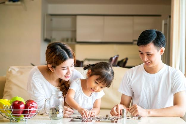 아시아 가족은 유리 은행에 동전을 넣어 돈을 절약 아시아 귀여운 소녀를 가르칩니다. 미래 계획, 재무 계획 또는 돈 투자 개념
