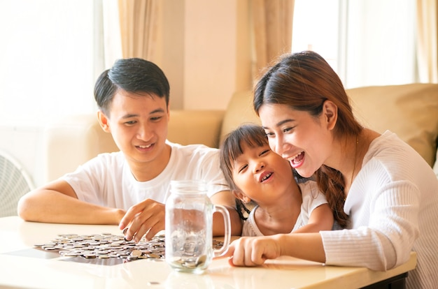 Asian family teach asian cute girl saving money putting coins into piggy glass bank, vintage tone. education, save money,