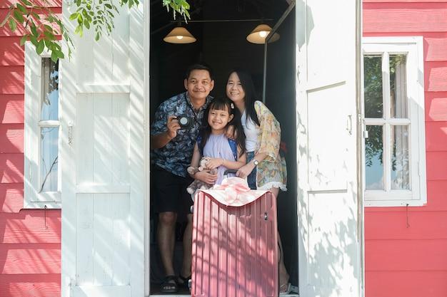 Азиатская семья путешествует и стоит в курортном отеле с улыбкой и счастливой