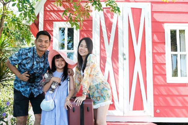 Азиатская семья путешествует и стоит возле курортного отеля с улыбкой и счастливой
