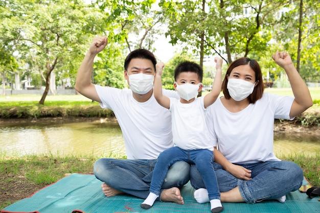 緑のパブリックガーデンの床に一緒に座ってマスクと手を振りながらアジアの家族。
