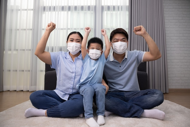 Азиатская семья в маске и поднятой руке сидит вместе на полу дома