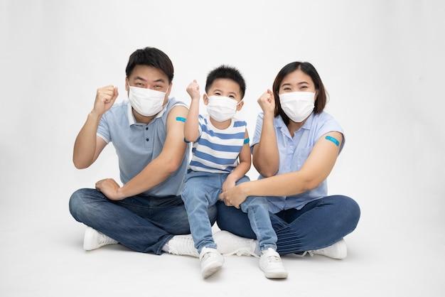 마스크를 쓰고 흰색 배경에 석고가 있는 팔을 보여주는 아시아 가족
