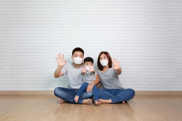 防護マスクを身に着けているアジアの家族とストップハンドサインを表示