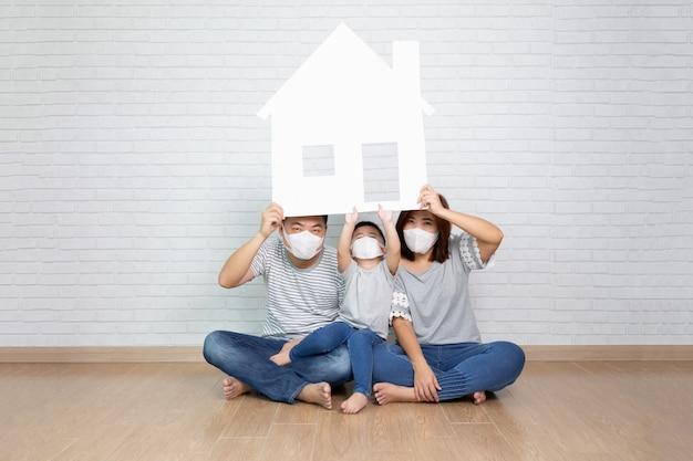 家に紙を保持している防護マスクを身に着けているアジアの家族