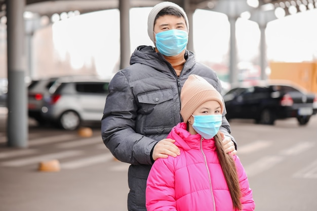 Asian family wearing protective masks on city street. concept of epidemic