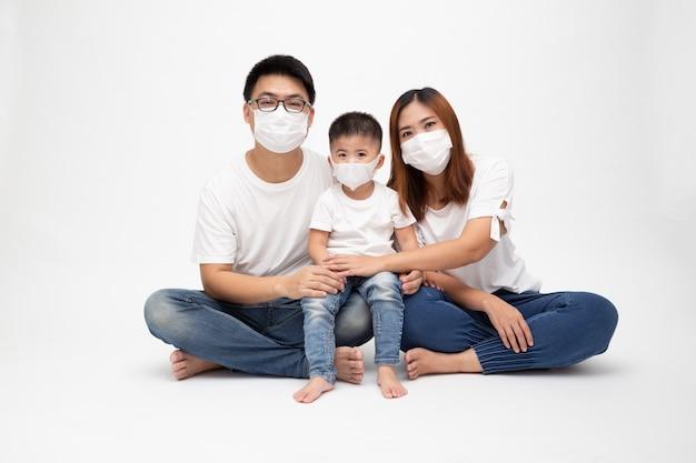 アジアの家族はウイルス武漢コビッド19を防ぐための防護医療用マスクを着用し、床に孤立した白い壁に一緒に座っています。汚染された空気の概念からの家族の保護