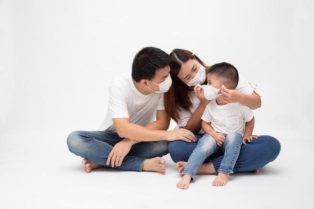 ウイルスを防ぐための保護医療マスクを身に着けているアジアの家族