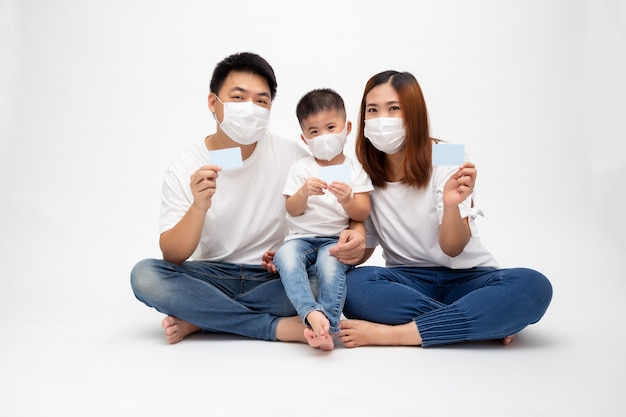 Asian family wearing protective medical mask for prevent virus covid-19 and holding insurance care card isolated on white wall. family protection and insurance medical card concept