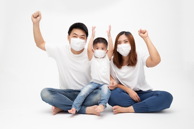 Asian family wearing protective medical mask for prevent virus wuhan covid-19 and hand up and sitting together on floor isolated white wall. family protection from contaminated air concept