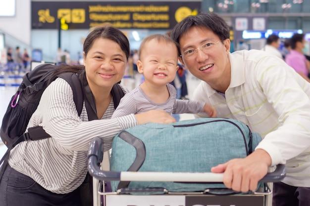 空港に搭乗する前に空港でかわいい幼児の男の子の子供を持つアジアの家族