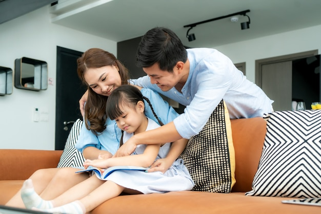 Asian family with father, mother and her daughter reading fairy tail story book on sofa at home