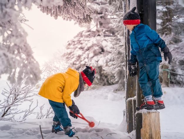 어린 소년과 소녀가있는 아시아 가족은 일본 센다이 자오 겨울 스키 리조트에서 즐거운 시간을 보내고 있습니다.