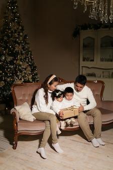 Азиатская семья с двумя детьми открывает подарки, сидя на диване у дерева ночью дома