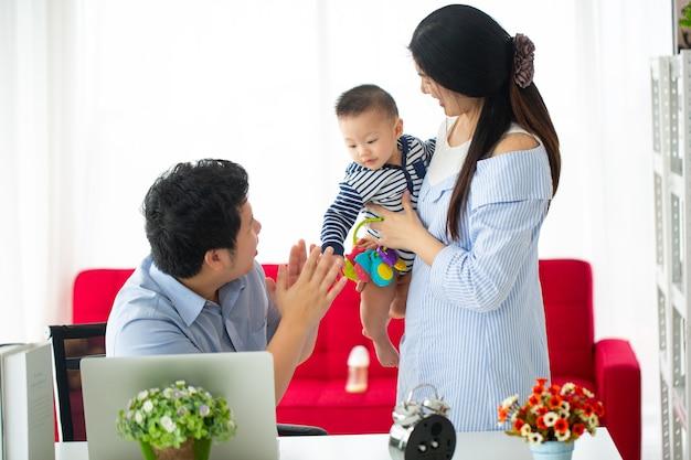 Азиатская семья работает дома занятые родители занимаются своим делом и вместе берут на дом ребенка в машине