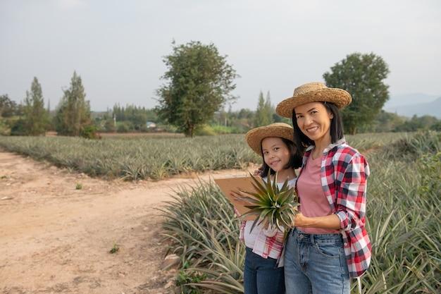 アジアの農家は、母と娘に農場でのパイナップルの成長を見てもらい、データをクリップボードの農家のチェックリストに保存します。