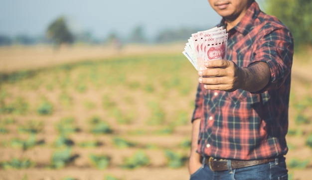 Asian farmer holding chinese banknotes