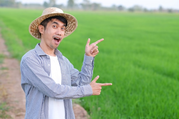 Asian farmer man pose surprise with wow shock face at a green rice farm