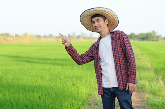 Asian farmer man smile and raise hand point to side at green rice farm