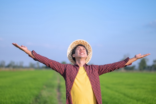 Asian farmer man smile and raised hands looking at a green rice farm