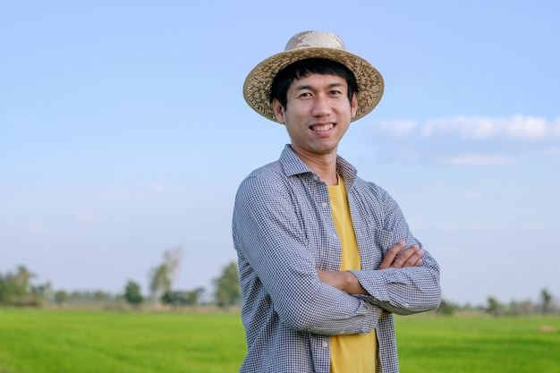 Asian farmer man standing cross arms and smile at a green rice farm