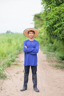 Asian farmer man wear a blue t-shirt and hat standing cross hands at the farm