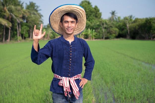 アジアの農家の男性は、伝統的な衣装を着て立って、緑の稲作農場で手の愛のサインを示しています