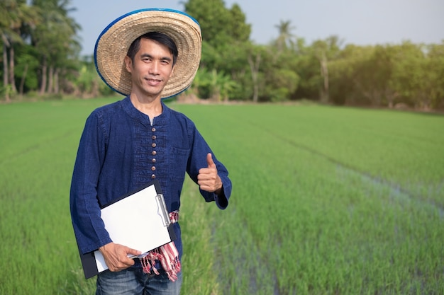 Asian farmer man wear traditional costume standing and hold paper board smile at green rice farm