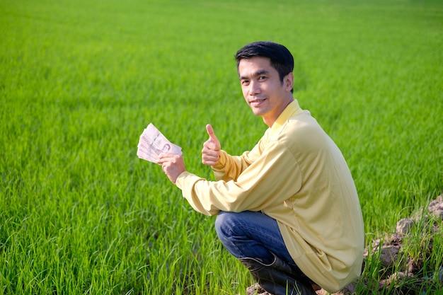 Азиатский фермер в желтой рубашке сидит и держит тайские банкноты на зеленой рисовой ферме.