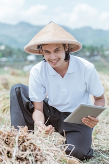 아시아 농부는 밭에서 태블릿 pc를 사용할 때 벼 수확량을 보여 주면서 미소를지었습니다.